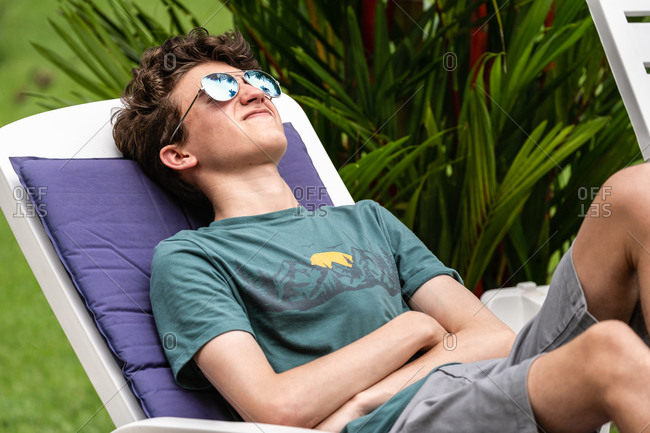 Teenage boy relaxing on lounge chair on vacation
