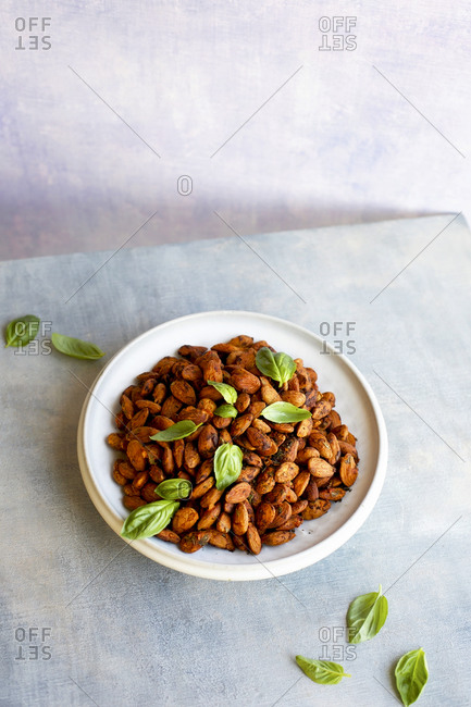 High angle view of tomato basil almonds on light background