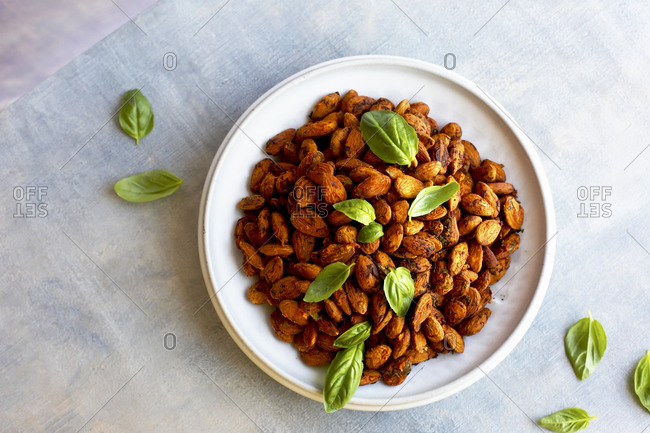 Overhead view of tomato basil almonds on light background