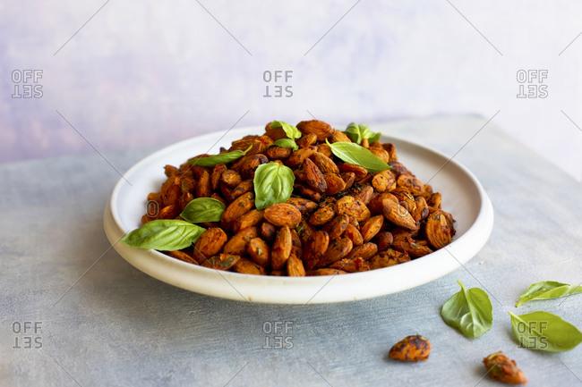 Tomato basil almonds on a plate on light background
