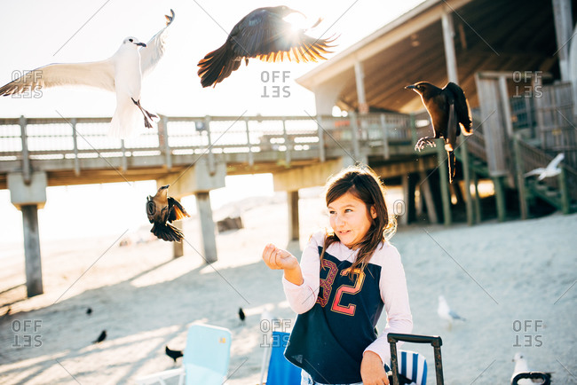 Girl looking nervous as birds fly around her while feeding them on a beach
