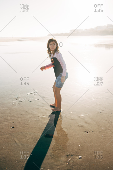 Girl walking barefoot in low tide on a beach