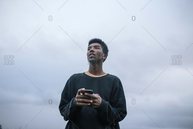 Teenager using his smartphone- low angle view