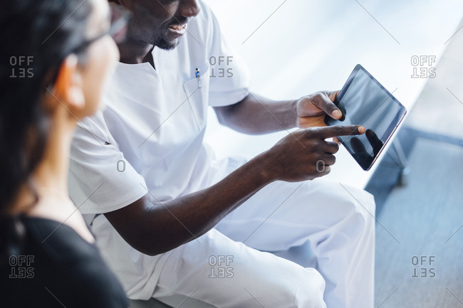 Dentist with tablet speaking with female patient in dental surgery
