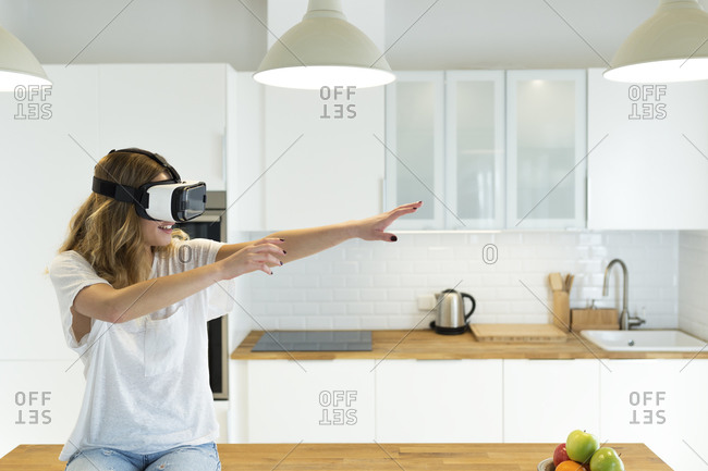 Female teenager in the kitchen with VR glasses