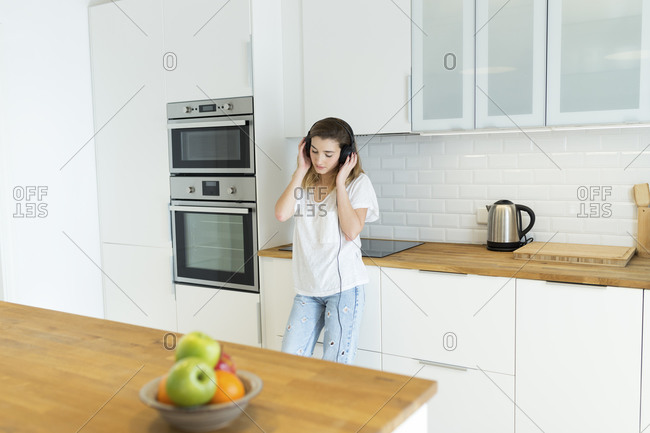 Female teenager with headphones in the kitchen