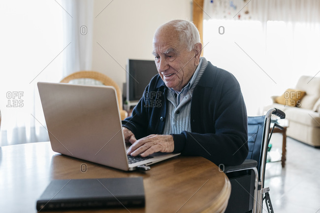 Portrait of content senior man in wheelchair using laptop at home