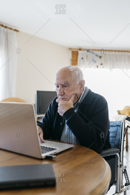 Portrait of senior man in wheelchair using laptop at home
