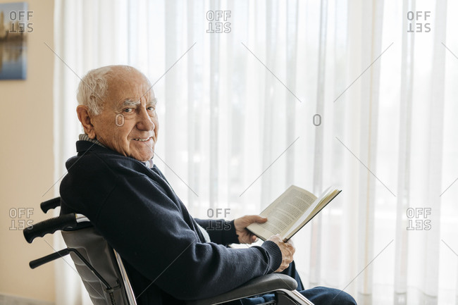 Portrait of smiling senior man sitting in wheelchair with a book