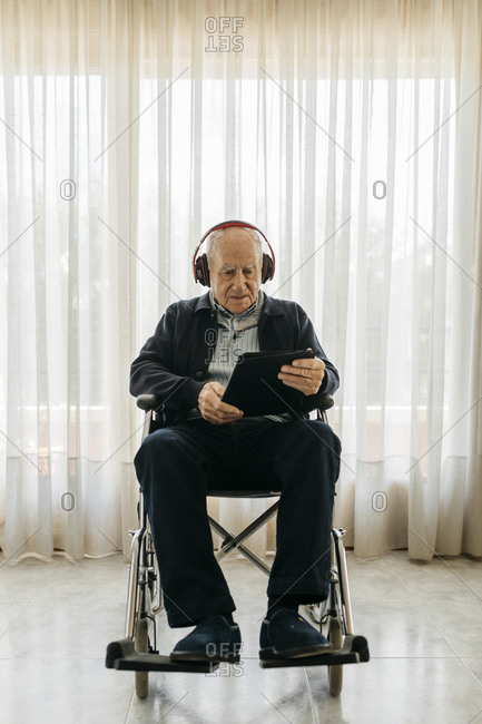 Portrait of senior man sitting in wheelchair using digital tablet while listening music with headphones