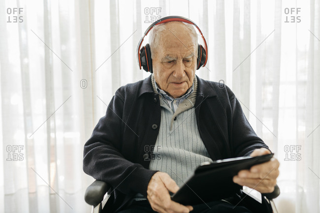 Senior man sitting in wheelchair reading using digital tablet while listening music with headphones