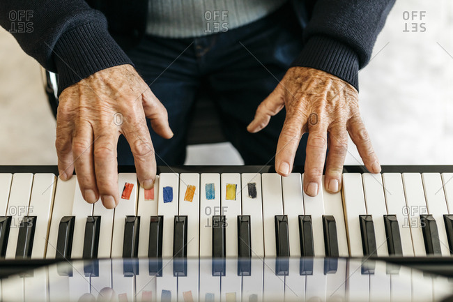 Hands of senior man playing piano- close-up
