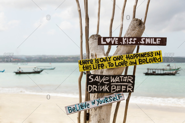 Indonesia- Bali- Jimbaran- Sign with motivational quotes standing on coastal beach