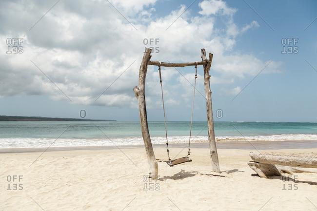 Indonesia- Bali- Jimbaran- Simple wooden swing on sandy coastal beach