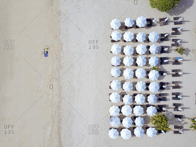 Indonesia- Bali- Aerial view of man sunbathing in front of rows of beach umbrellas on sandy coastal beach of Nusa Dua