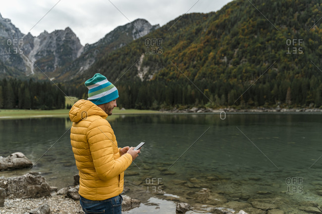 Hiker using smartphone at Laghi di Fusine- Friuli Venezia Giulia- Italy
