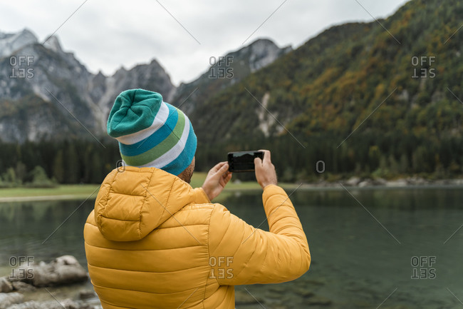 Hiker using smartphone and taking a picture at Laghi di Fusine- Friuli Venezia Giulia- Italy