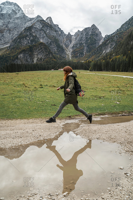 Female hiker jumping over puddle- Friuli Venezia Giulia- Italy