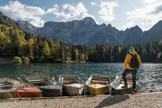 Hiker standing at mooring area with boats at Laghi di Fusine- Friuli Venezia Giulia- Italy