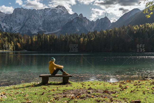 Hiker sitting on bench at Laghi di Fusine- Friuli Venezia Giulia- Italy