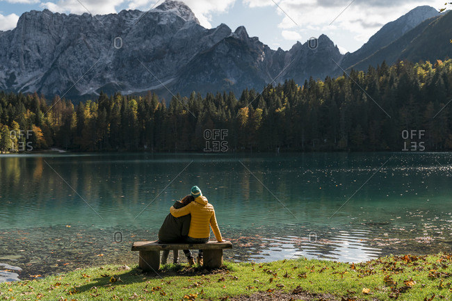 Rear view of couple sitting on bench at Laghi di Fusine- Friuli Venezia Giulia- Italy