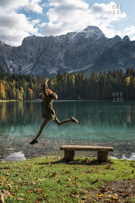 Female hiker jumping from bench at Laghi di Fusine- Friuli Venezia Giulia- Italy