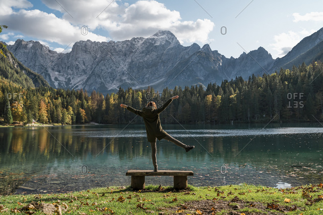 Rear view of female hiker standing on one leg on a bench at Laghi di Fusine- Friuli Venezia Giulia- Italy