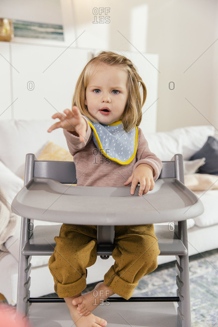 Little girl sitting on high chair at home reaching out