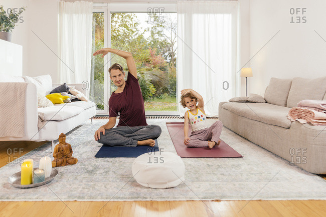 Father and daughter doing yoga together at home