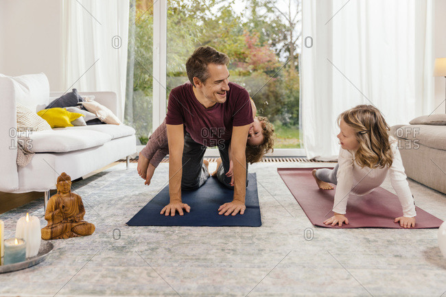 Father with daughters doing yoga in living room at home