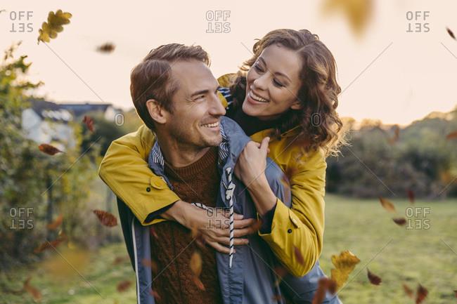 Man giving woman a piggyback ride outdoors in autumn