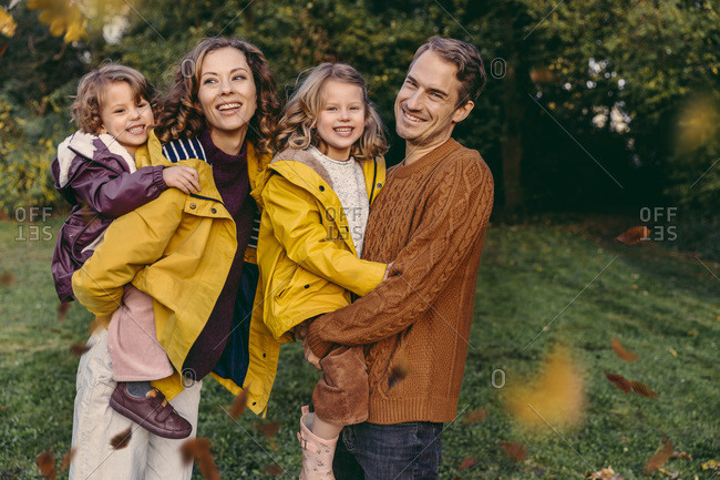 Portrait of happy family with two daughters outdoors in autumn