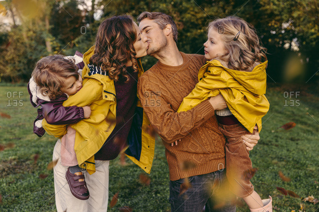 Couple kissing outdoors in autumn watched by her daughters