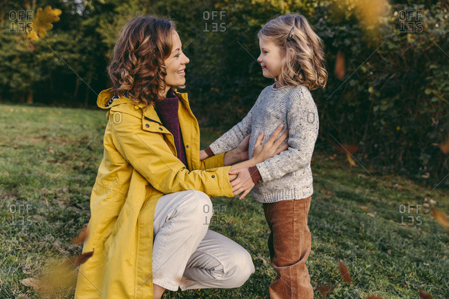 Smiling mother with daughter on a meadow in autumn