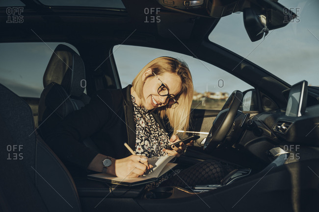 Young blond woman using smartphone in the car- writing in a notebook