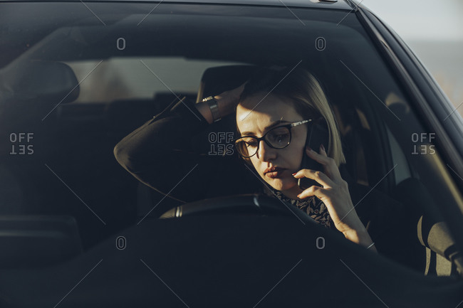 Young blond businesswoman using smartphone in the car