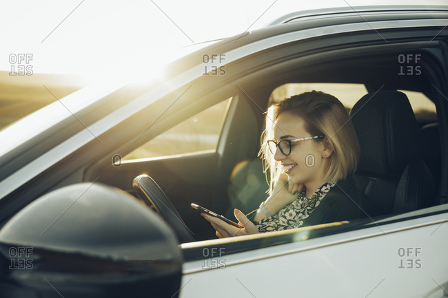 Young blond woman using smartphone in the car