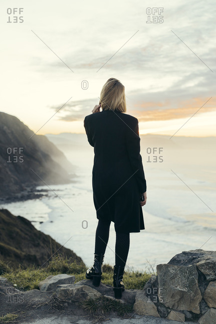 Rear view of young blond woman with smartphone at the coast during sunset