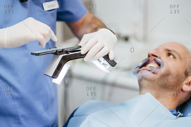 Close-up of dentist taking photo of dentures with special photographic apparatus