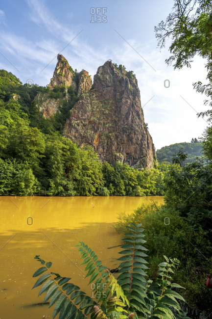 Germany- Rhineland-Palatinate- Bad Munster am Stein-Ebernburg- Yellow Nahe river with Rheingrafenstein rock formation in background