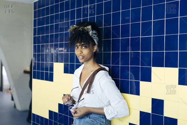 Portrait of young woman with curly black hair leaning against tiled wall