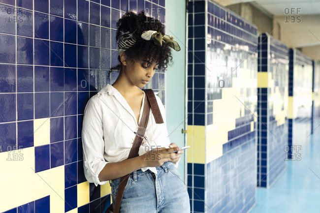 Portrait of young woman with curly black hair leaning against tiled wall text messaging