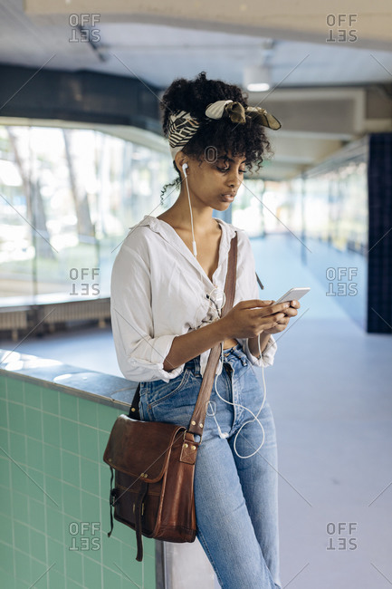 Portrait of young woman with earbuds looking at cell phone in a passage