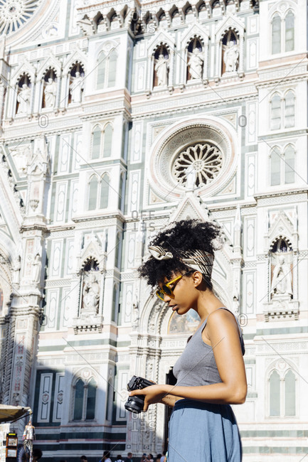 Young woman with camera standing in front of cathedral- Florence- Italy