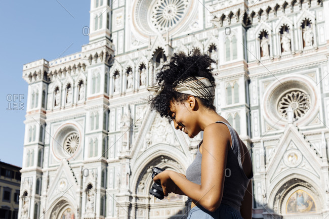 Smiling young woman looking at her camera in front of cathedral- Florence- Italy