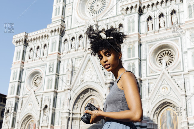 Portrait of young woman with camera in front of cathedral- Florence- Italy