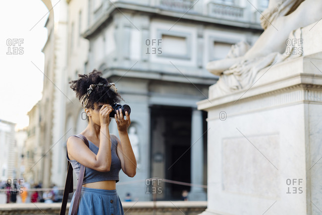 Young woman taking photo with camera- Florence- Italy