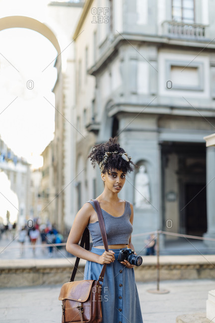 Portrait of young woman with camera exploring the city- Florence- Italy