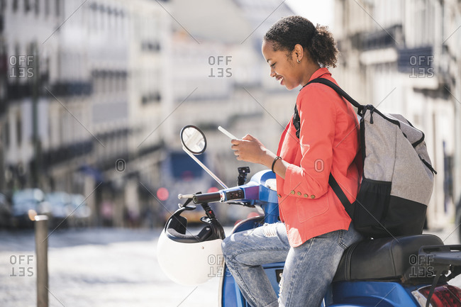 Young woman using cell phone on motor scooter in the city- Lisbon- Portugal