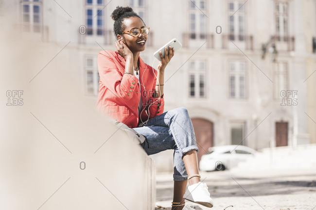 Smiling young woman with earphones and smartphone in the city- Lisbon- Portugal